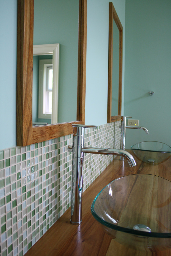 Green glass mosaic tile over handcrafted vanity with glass bowl vessel