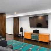 Basement design - home theatre with hardwood floor, mounted flatscreen, black leather seats and surround sound.