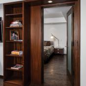 Basement design - Custom cabinetry and mahogany interior doors lead to guest suite