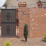 Brick privacy fence with wrought iron gate