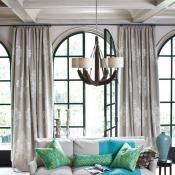 Chandelier lighting in living room. Accent colors of blue and green adds pops of color to the neutral color walls and furniture