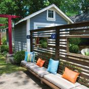 Backyard with custom built-in bench with colorful pillows