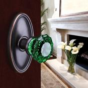 The door is slightly ajar revealing a fireplace with a vase of lilies. The door knob is a beautiful emerald green.