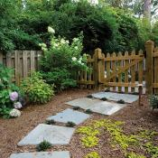 Fenced yard with wood barn-style gate and large pavers for walkway