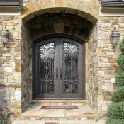 front of home with stone exterior and wrought iron front door