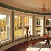 Window wall design idea with a set of 4 windows. The beige of the windows is complemented by the dark green of the walls