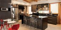 Modern kitchen with glossy cabinets and stainless steel accents and mosaic tile