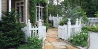 Curb appeal, a white fence, paved walkway, evergreen and flowers