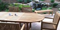 Outdoor teak furniture on patio with a beautiful landscape and water feature in the background