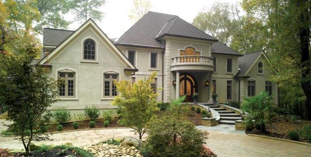 Front exterior of home with a garden, beautiful window and door design and a balcony off the second floor