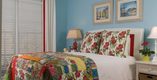 Guest bedroom design with blue walls and accent colors of red and blue