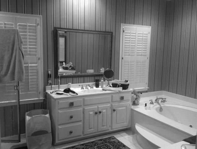 Old outdated wallpaper and floors in the master bathroom